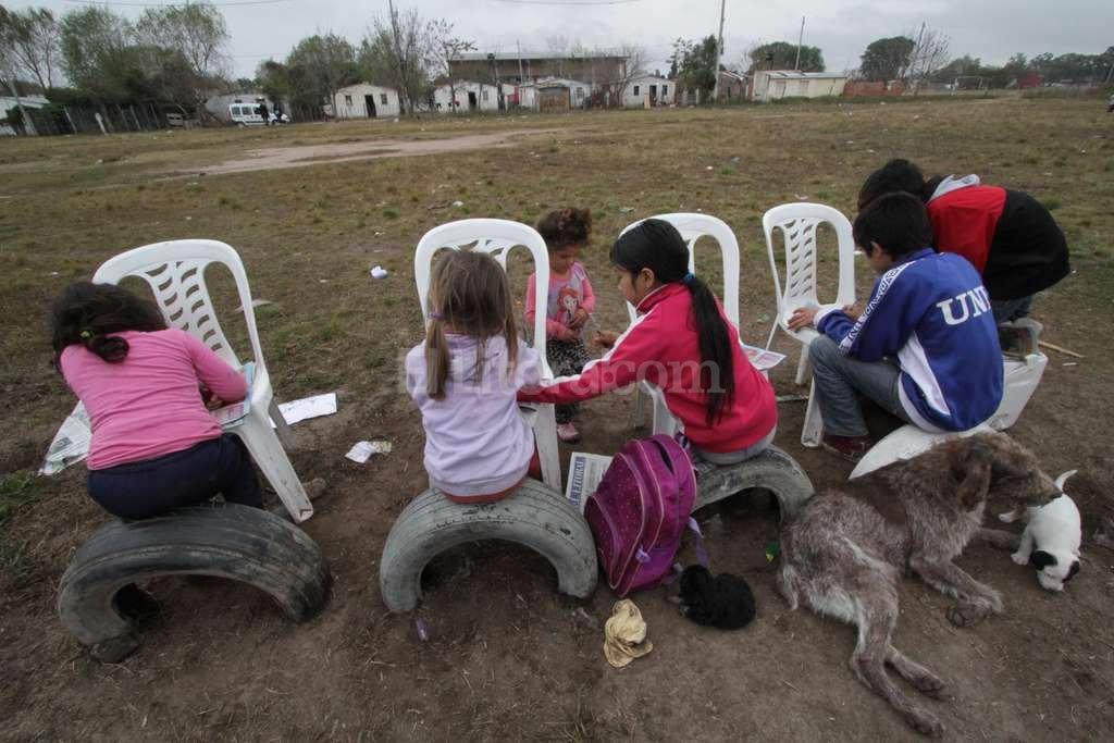 """Son chicos y quieren jugar. Noelia, Yuliza, Nicole y David, los cuatro chicos que estaban """"practicando las letras"""" en el predio donde desean tanto un espacio con juegos. Crédito: Mauricio Garín"""