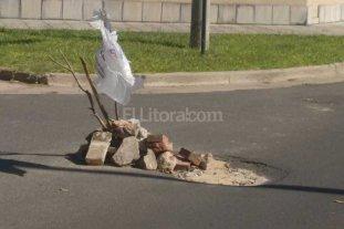 Tapan baches con escombros y bolsas