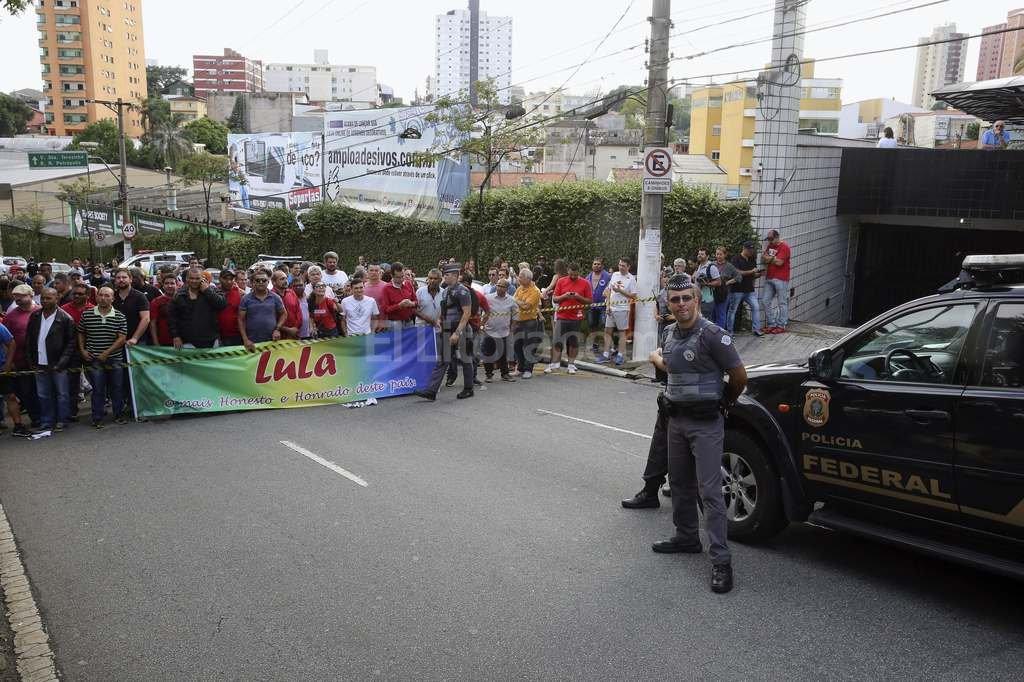 Agentes de Policía y ciudadanos con pancartas ante la residencia de Lula en la ciudad de Sao Bernardo do Campo. Crédito: EFE