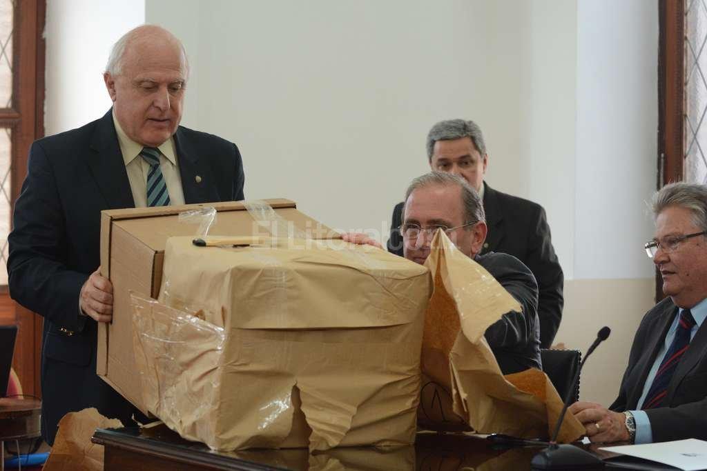 El gobernador abre la caja con el primer sobre. Hubo cinco oferentes para la obra. Foto:Luis Cetraro