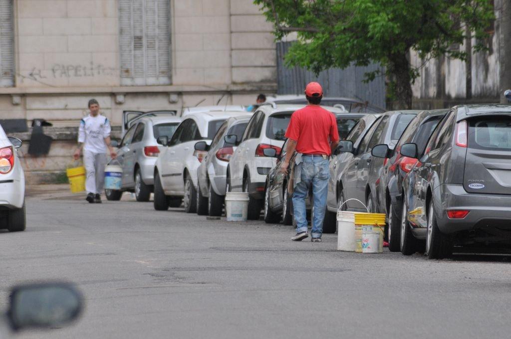 Cuidadores de vehículos con baldes con agua para lavar autos, en inmediaciones del viejo Hospital Italiano. Crédito: Flavio Raina /Archivo El Litoral
