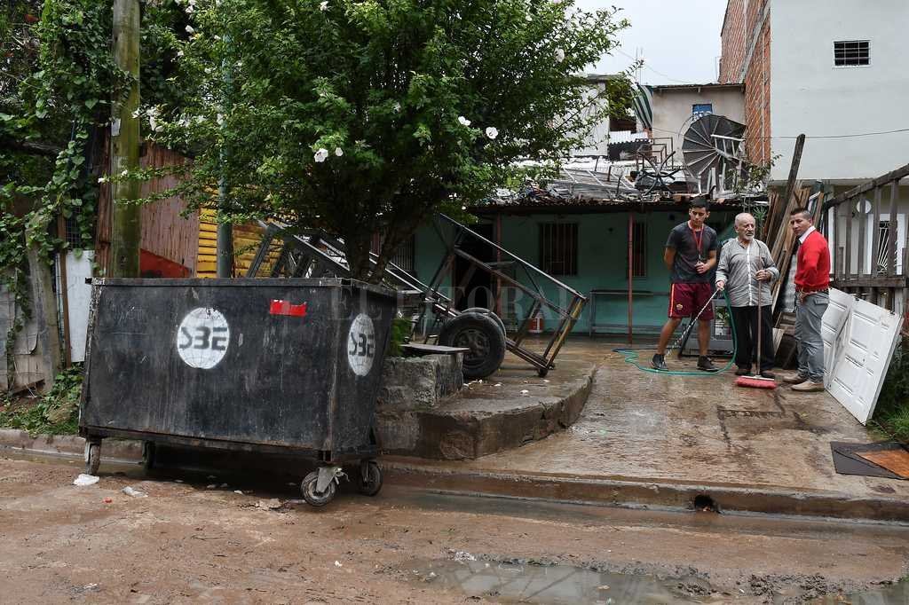 Un vecino riega frente al contenedor donde fue encontrado el cuerpo de un adolescente en el barrio porteño de Villa Soldati. <strong>Foto:</strong> Télam