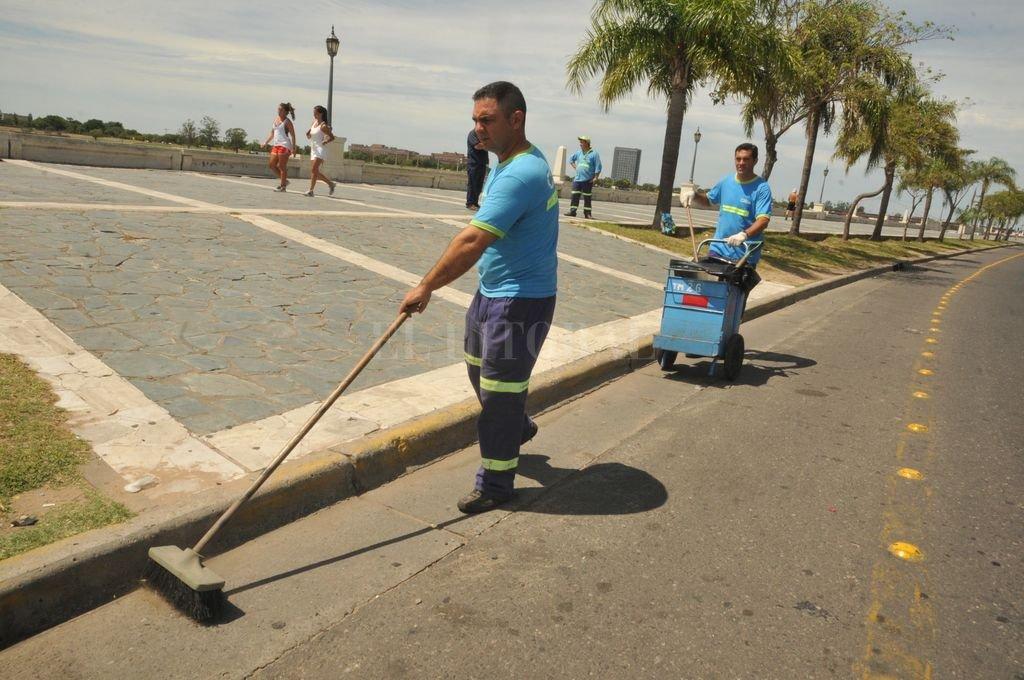 El faro. Alberto Ramos (adelante) y Jorge Suárez, que hace más de una década que trabajan para Cliba, barren uno de los tramos de la costanera que los fines de semana más basura acumula. Guillermo Di Salvatore