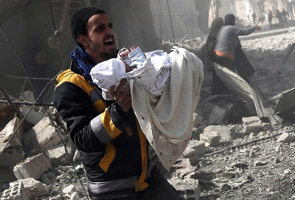 Un bebé es rescatado del bombardeo. Crédito: Télam