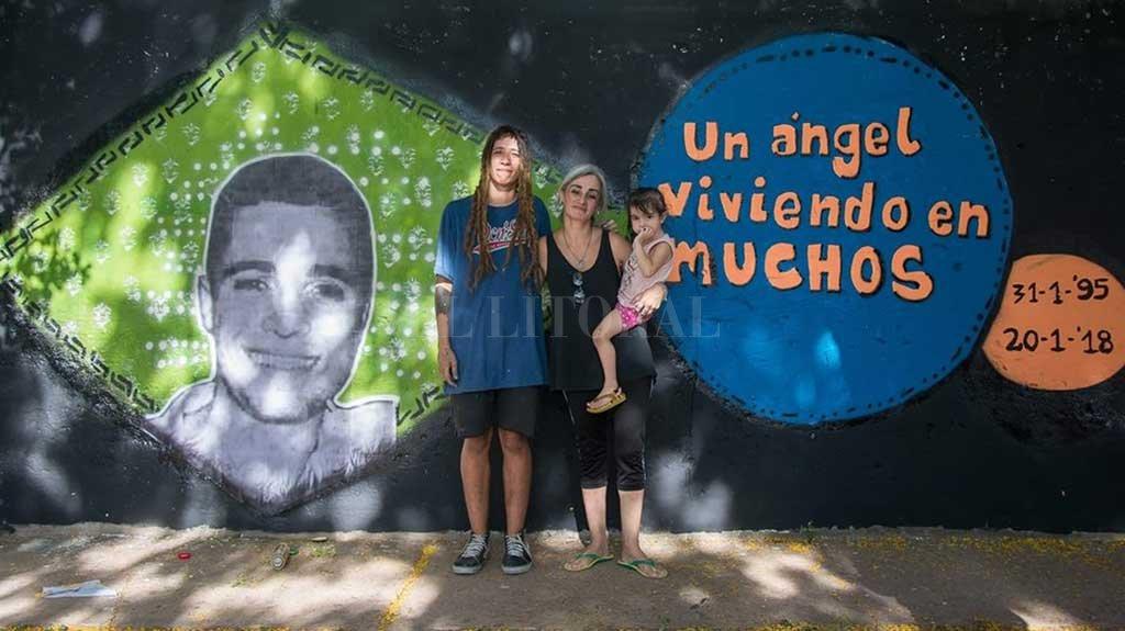 Entre todos. Unas 70 personas colaboraron para pintar este mural que lo recuerda, creado en una pared ubicada en la intersección de las calles Derqui y Centenario de Santo Tomé. El dibujo fue coordinado por la artista local Yamila Caporizzo (izquierda), quien en la foto posa junto a Alejandra D'Ambra, mamá de Augusto.  <strong>Foto:</strong> Gentileza