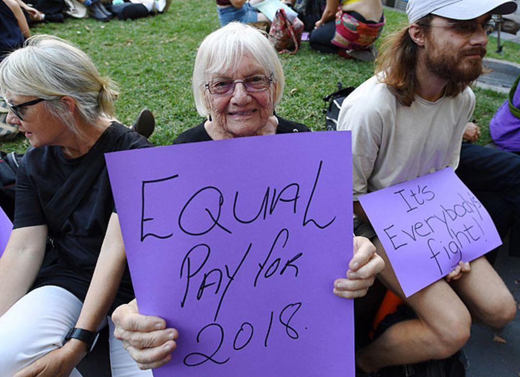 Una australiana pide igual salario para mujeres y hombres, junto a un joven que subraya que es una lucha de todos, en la concentración del Día de la Mujer en Melbourne.  Crédito: EFE / JOE CASTRO