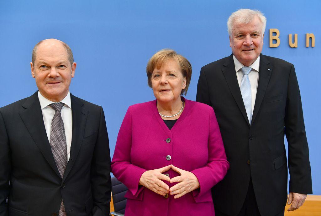 De izquierda a derecha, el presidente interino del Partido Socialdemócrata (SPD), Olaf Scholz, la canciller alemana, Angela Merkel, y el líder de la Unión Cristianosocial (CSU), Horst Seehofer, el 12/03/2018 en Berlín, Alemania, durante la firma del contrato de coalición para el nuevo Gobierno entre conservadores y socialdemócratas. Crédito: DPA