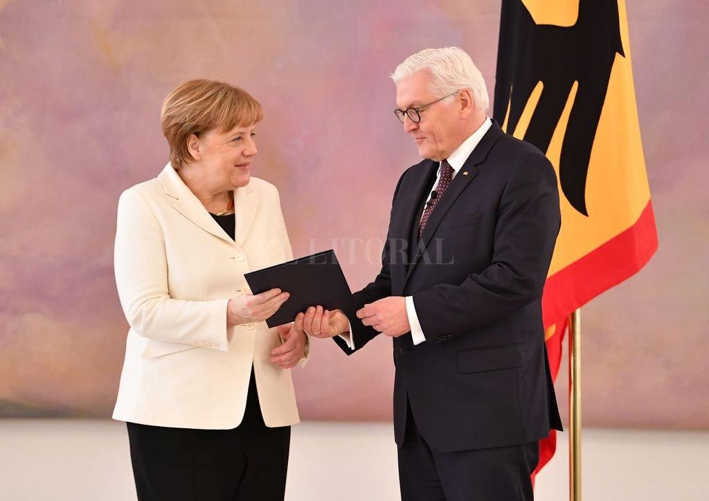 El presidente federal de Alemania, Frank-Walter Steinmeier (der.) nombra a la líder conservadora, Angela Merkel, canciller del país en el Palacio de Bellevue, en Berlín, Alemania, el 14/03/2018 Crédito: DPA