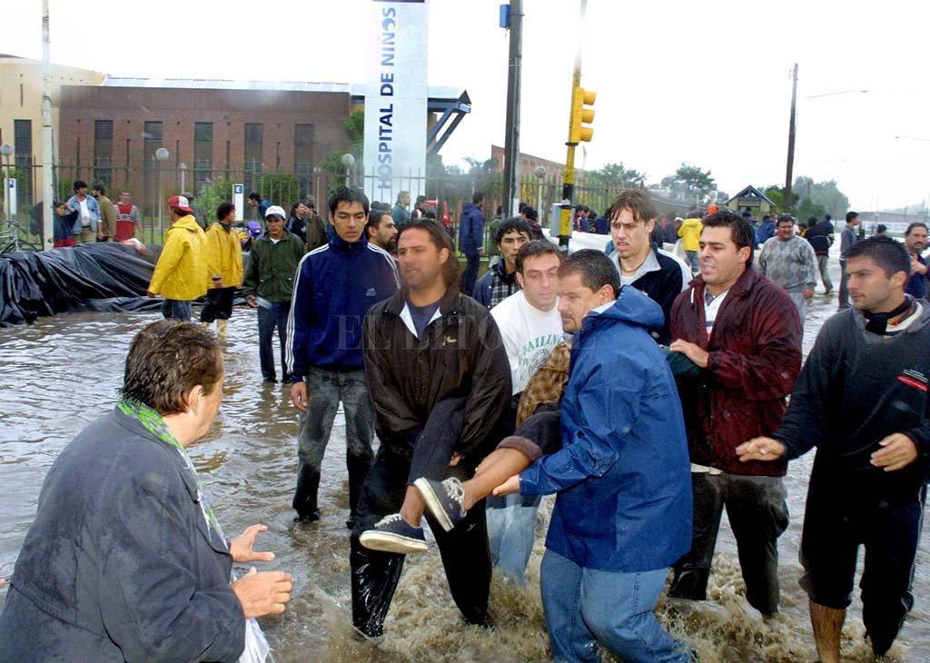 El registro gráfico (del 6 de mayo de 2003) muestra a una persona que es rescatada desesperadamente por voluntarios. Ocurrió frente al Hospital de Niños. <strong>Foto:</strong> Archivo El Litoral.