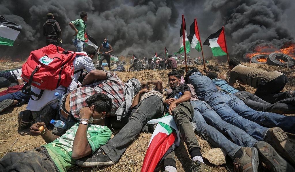 Manifestantes palestinos se cubren durante los enfrentamientos con las fuerzas de seguridad israelíes en Jan Yunis,Territorios Palestinos. Las protestas palestinas se dan en el marco del 70 aniversario de la fundación del Estado de Israel y el día de la Nakba (catástrofe). Los palestinos reclaman su derecho a volver a su antiguo territorio. <strong>Foto:</strong> DPA