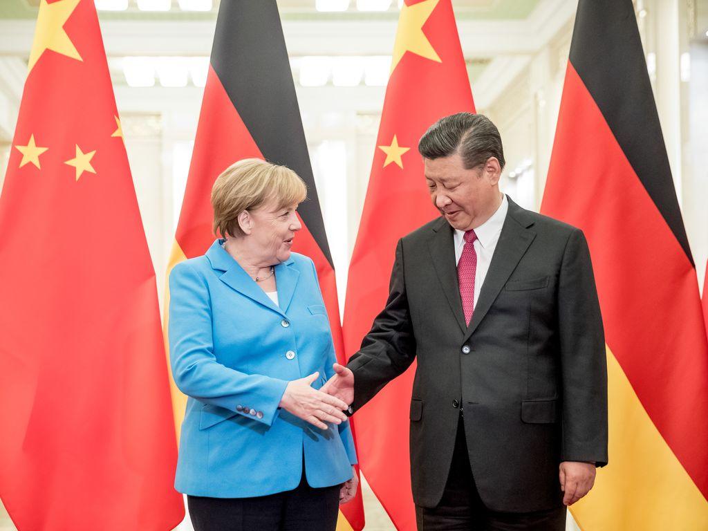 La canciller alemana, Angela Merkel, se saluda con el presidente chino, Xi Jinping (der.) el 24/05/2018 en Pekín, China. La mandataria subrayó la importancia de encontrar soluciones internacionales para resolver las crisis mundiales.  <strong>Foto:</strong> Michael Kappeler/dpa