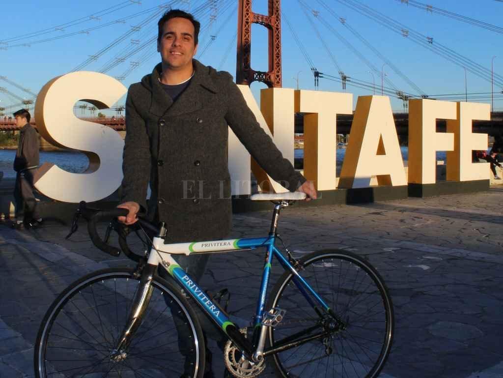 Símbolo. Joaquín, junto a su compañera, la bici, y el Puente Colgante, antes de la partida a Dinamarca. Crédito: Gentileza.