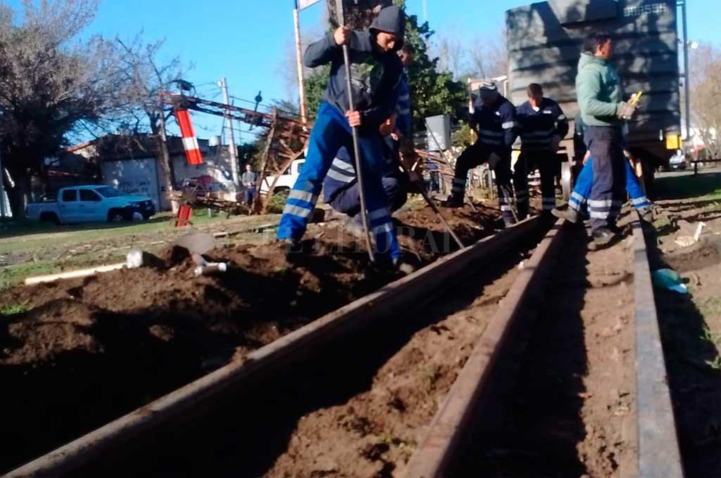 """La cuadrilla del Belgrano Cargas primero tiene que alinear la vía —que se desplazó por el descarrilamiento— con la trocha y luego volver a """"encarrilar"""" el tren. Crédito: Mauricio Garín"""