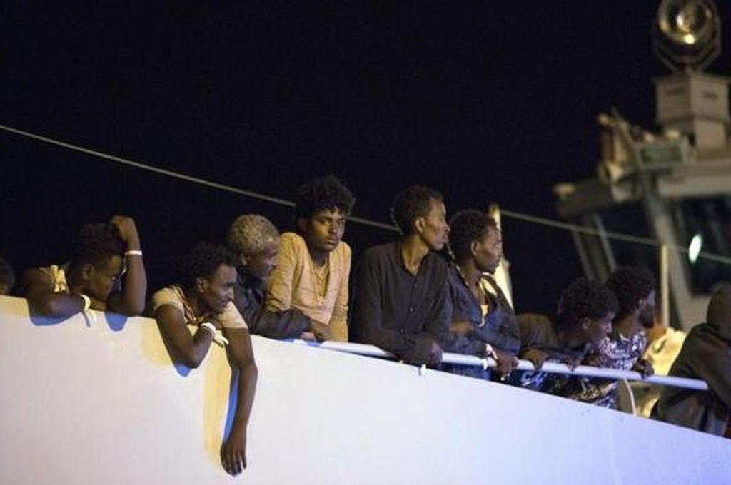 Varios migrantes esperan antes de desembarcar de la nave de Frontex. Crédito: FRANCESCO RUTA.