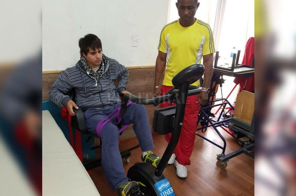 En plena rehabilitación. Bruno Escobar se ejercita en la bicicleta que le fabricaron los estudiantes. Junto a él, Benito, el kinesiólogo cubano quien sigue de cerca su tratamiento.