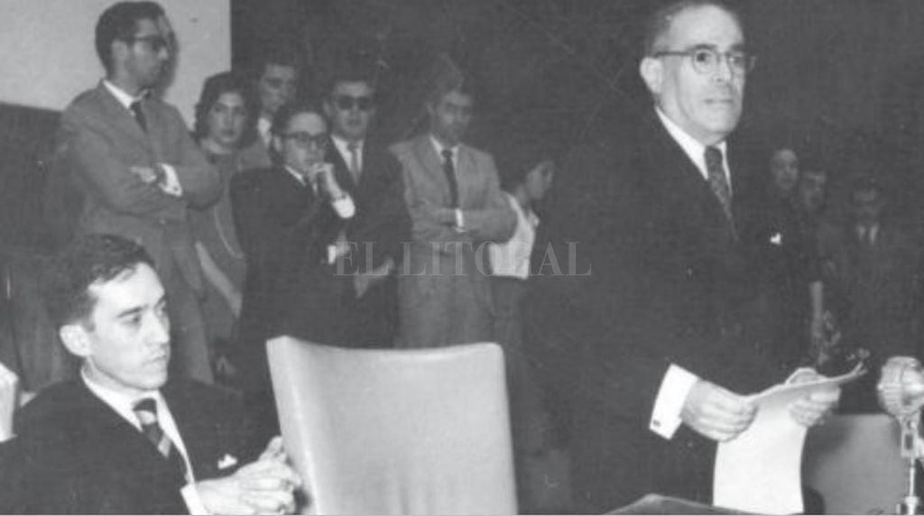 El rector Josué Gollán lee su discurso ante un Paraninfo de la UNL repleto. A su lado, un joven Fernando Birri escucha con atención. Crédito: Archivo El Litoral