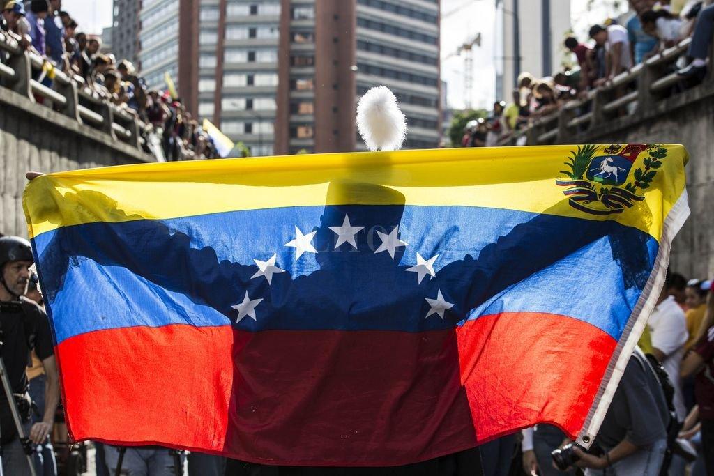 Una persona extiende una bandera venezolana ante decenas de manifestantes durante una protesta antigubernamental.  Crédito: Archivo