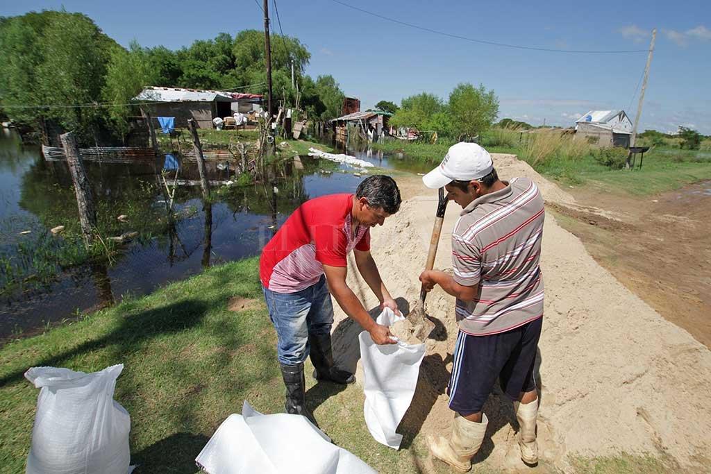 """Todos a """"bolsear"""". Con bolsas de arena se hacen caminos para ingresar a las viviendas. Crédito: Pablo Aguirre."""