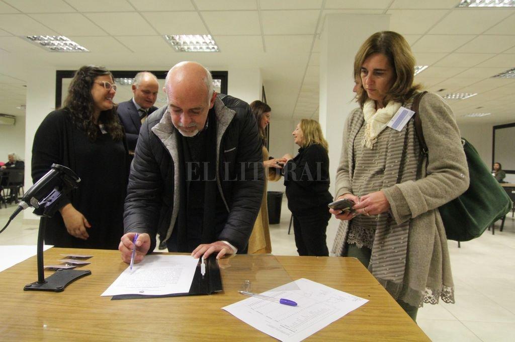 Ricardo Paulichenco, uno de los apoderados de Juntos y Mariela Uberti (Cambiemos) firmando las actas respectivas del escrutinio definitivo. <strong>Foto:</strong> Pablo Aguirre