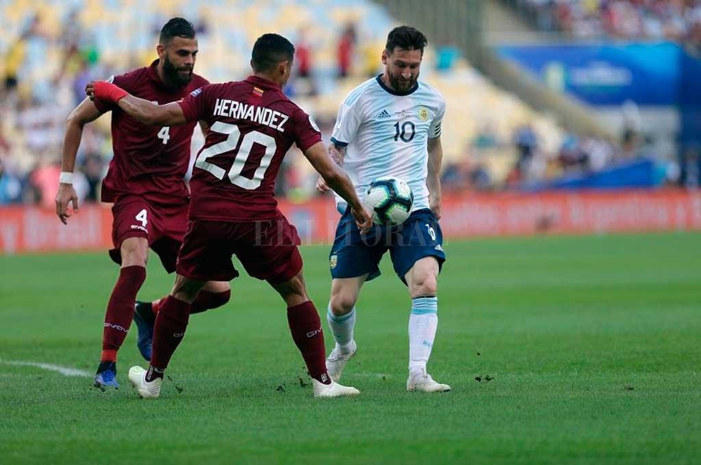 Siempre rodeado. Messi intenta eludir la marca de dos venezolanos. <strong>Foto:</strong> Twitter Selección Argentina
