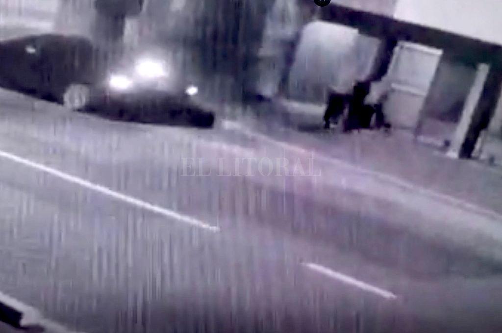 Momento en el que dos delincuentes violentan la entrada al edificio mientras un tercero los espera en el auto. <strong>Foto:</strong> Captura digital