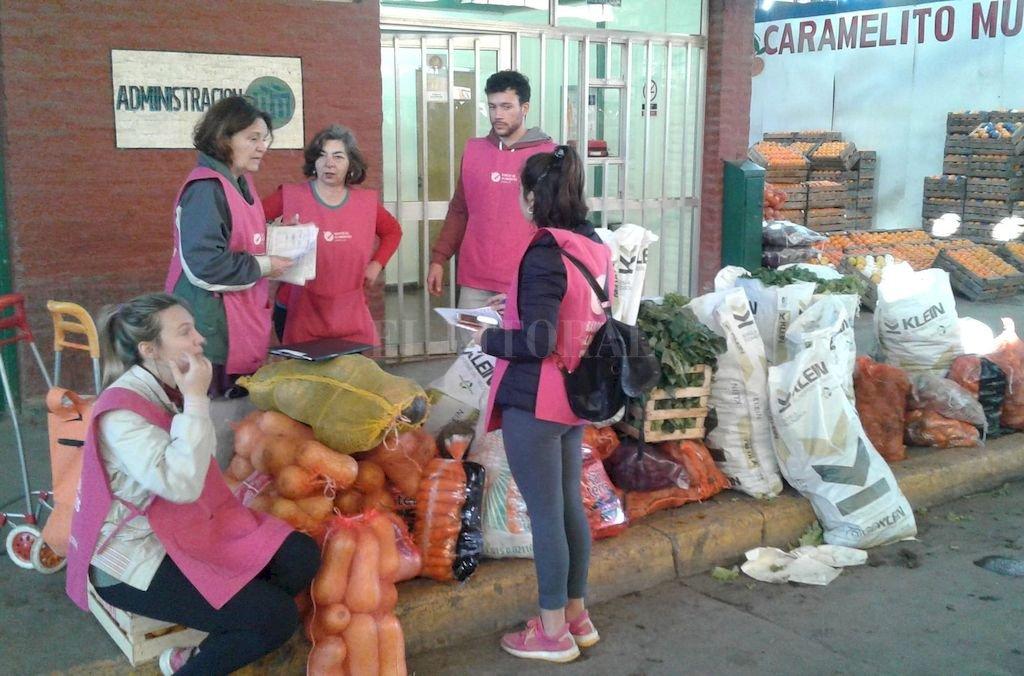 Los voluntarios afinan en las fichas de registro los kilos de verduras y frutas colectados ese martes en el Mercado de Productores. Al trabajo lo realizan con mucha pasión, pero también con disciplina y minuciosidad. <strong>Foto:</strong> Gentileza