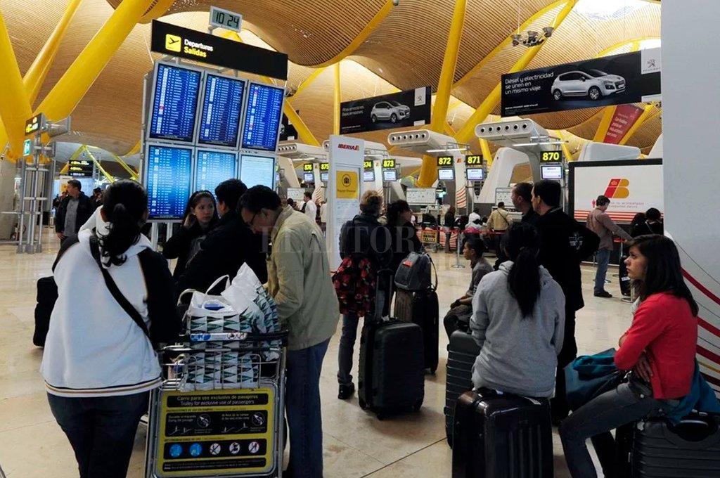 Pasajeros realizan una fila en Barajas para hacer los trámites de inmigración antes de ingresar a España.  <strong>Foto:</strong> AFP.