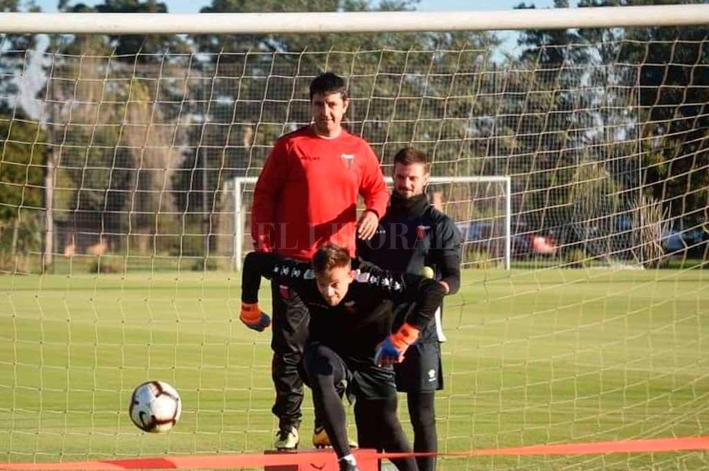 """En Modo """"Cachorro"""" . El gesto del golero charrúa Leo Burián marca de qué manera entrena y lo entrenan al """"1"""" sabalero. La foto, con Franco Saita observando (es el de rojo que aparece atrás), resume todo: el elástico, el pie apoyado en la línea como ahora exige la FIFA, la mirada atenta y los ojos clavados en la pelota. Por lo visto, da resultados. <strong>Foto:</strong> Prensa Club Atlético Colón"""