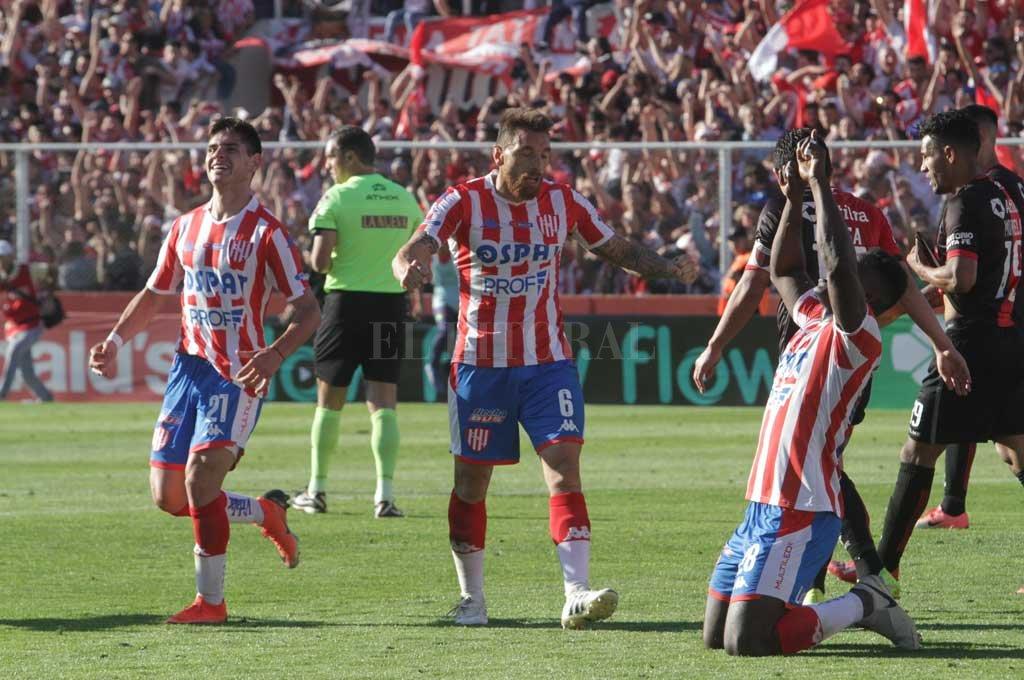 Gómez Andrade, la figura del clásico, se arrodilla y eleva sus brazos al cielo; Bottinelli se acerca a abrazarse con él y el pibe Comas festeja con una sonrisa. Crédito: Mauricio Garín