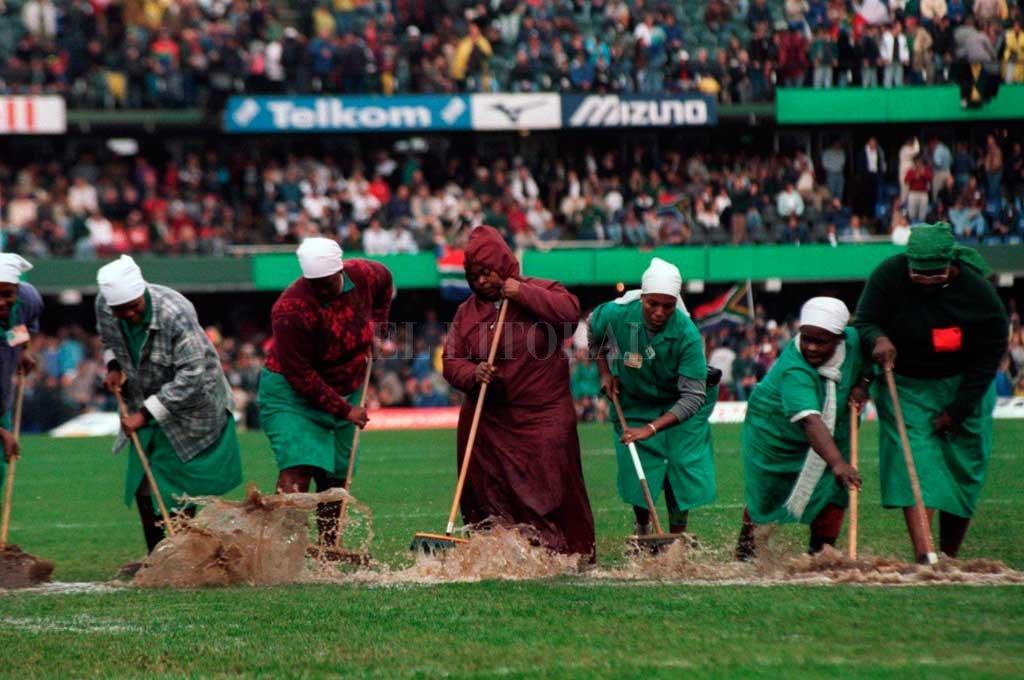 Mundial 1995. Voluntarias sudafricanas sacan el agua del estadio de Durban, donde horas después, los locales vencerían por semis a Francia por 19 a 15 para acceder al partido decisivo ante Los All Blacks. La final también quedaría en poder de los Springboks coronándose, de esa manera, por primera vez campeones del mundo. <strong>Foto:</strong> World Rugby