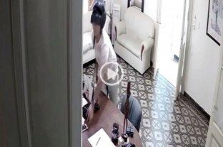 Video: Entró a una clínica y mirá lo que se llevó - Momento en que el delincuente toma el teléfono que estaba sobre el escritorio. -