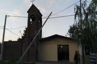 Un poste de telefonía a punto de caerse sobre una capilla en barrio El Arenal - Peligro. Los vecinos improvisaron con un palo un sostén para que el poste no continúe cayendo. -