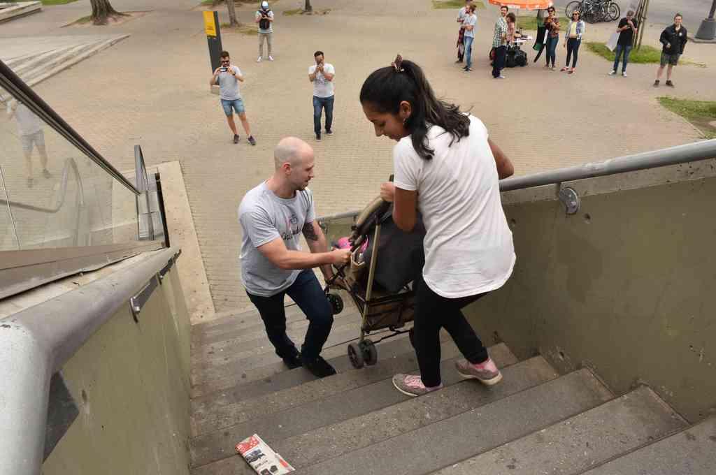 Ardua tarea. Dos jóvenes suben con dificultad a un niño que está en un cochecito, en la escalera del puente peatonal de Alem y Tucumán.  <strong>Foto:</strong> Flavio Raina