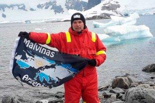 """Fin de la travesía: el excombatiente que recorrió la Antártida retorna a Ushuaia - Orgullo. Navas hace flamear la bandera """"malvinense"""". De fondo, los bloques de los hielos australes. -"""