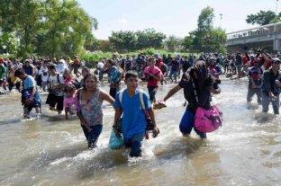 Una ola de migrantes cruza de Guatemala a México a través de un río