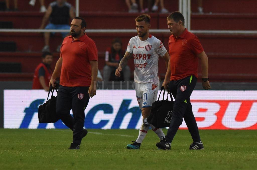 Jalil Elías se va de la cancha luego de ser atendido por el doctor Santiago Calvo y el kinesiólogo Sergio Magnín. Todavía siente dolores en la espalda y no se sabe si llegará en condiciones. Crédito: Mauricio Garín
