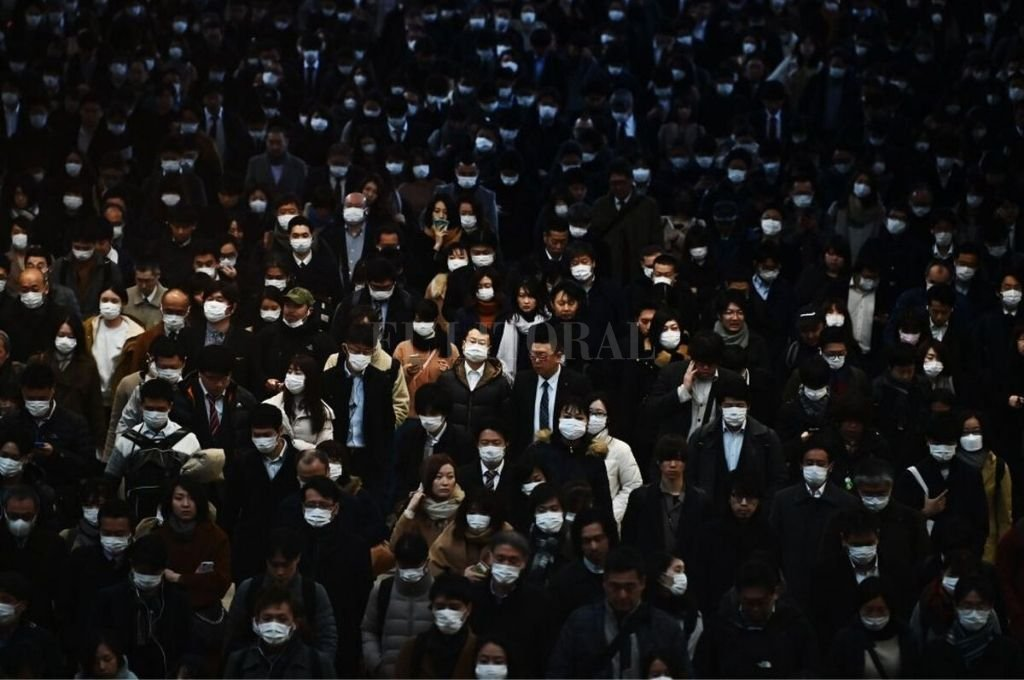 Postal de Tokio. Ciudadanos ingresan en la estación de trenes de Shinagawa, luego de cumplir con sus diarias tareas. Muchos de ellos, utilizando mascarillas de protección.   Crédito: Xinhua