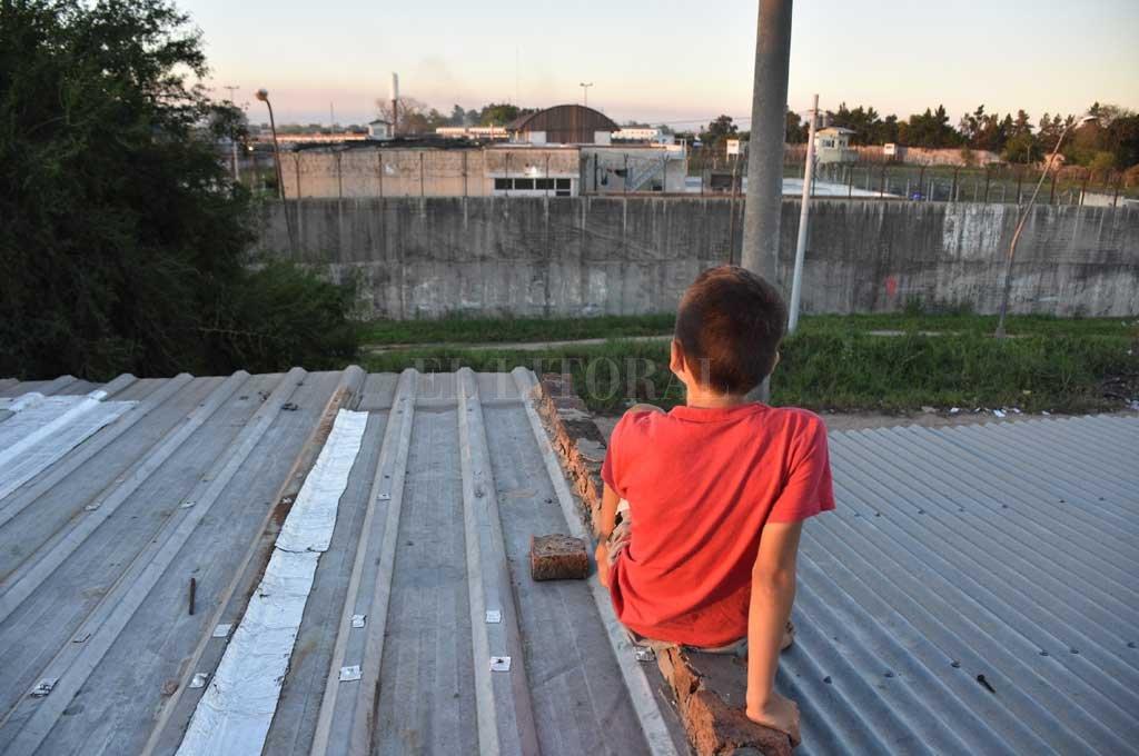 Entender. El niño curiosea desde el techo de su hogar el motín del lunes en Las Flores. Hay que ayudarlos a expresar sus sentimientos, en la rutina y animarlos a jugar y realizar actividades, recomiendan. Crédito: Pablo Aguirre