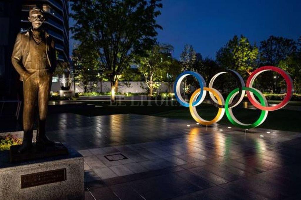El barón Pierre de Coubertin, responsable de los Juegos Olímpicos Modernos, y los anillos que integran a los cinco continentes. Habrá que esperar por lo menos un año más para la cita de Tokio.     Crédito: Archivo
