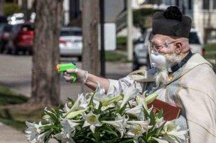 Un sacerdote bendice a los feligreses con una pistola de agua para respetar la distancia social