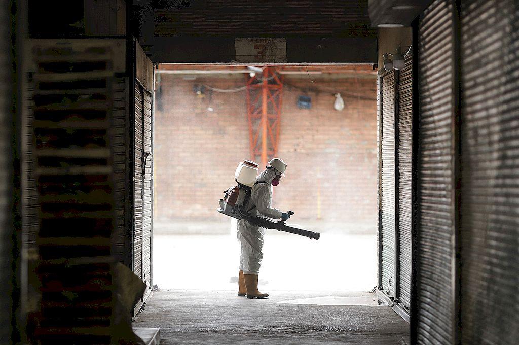 Un trabajador porta un traje protector y una mascarilla mientras realiza un proceso de nebulización durante una jornada de limpieza y desinfección en la central de abastecimiento de alimentos Corabastos, en Bogotá. Crédito: Xinhua/Jhon Paz