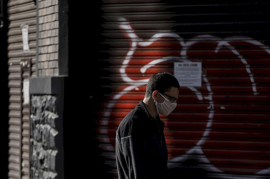 Un hombre porta un barbijo mientras camina frente a tiendas cerradas en Sao Paulo. Crédito: Xinhua/Rahel Patrasso