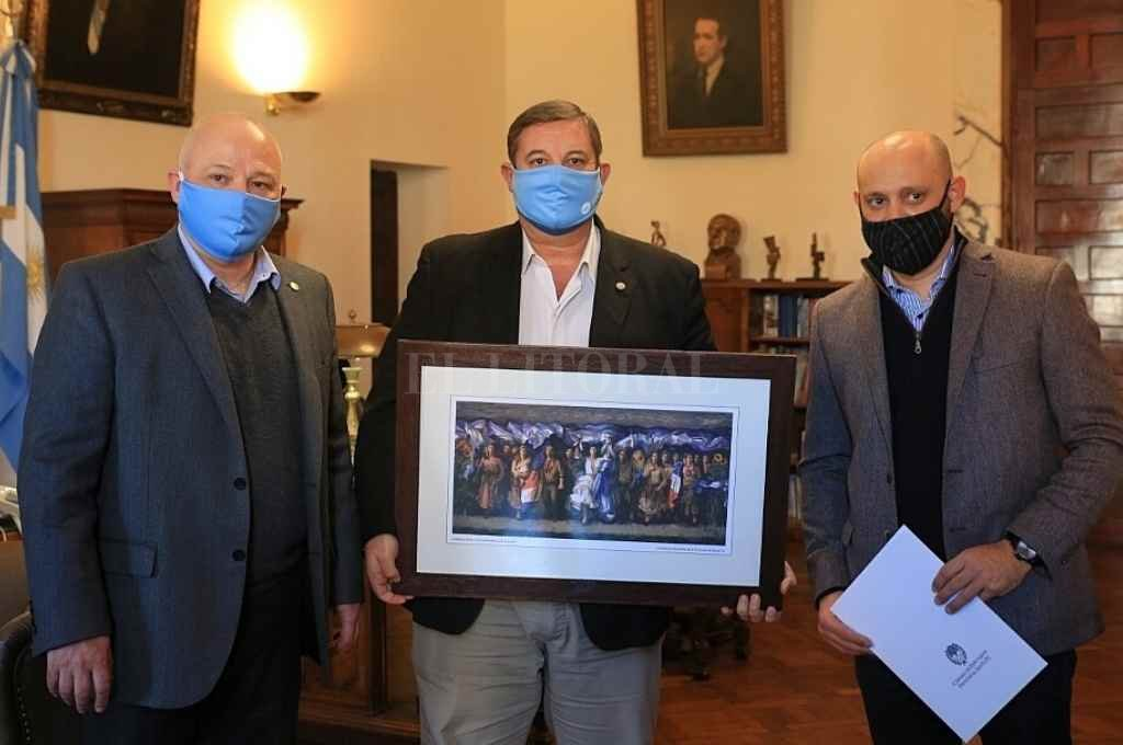 Gustavo Puccini, secretario Parlamentario de la Cámara de Diputados entregó al rector de la UNL, Enrique Mammarella, un reconocimiento por haberle facilitado el uso del Paraninfo para las sesiones del cuerpo durante los primeros meses de la pandemia.    Crédito: Cámara de Diputados