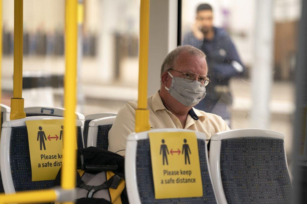 Un hombre portando una mascarilla viaja en un tranvía, en la Estación de Ferrocarril Manchester Victoria, en Manchester Crédito: Gentileza