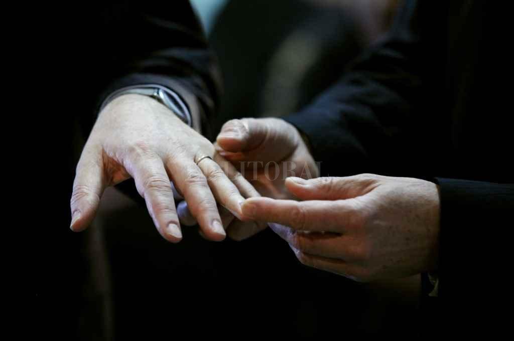 El registro gráfico es del 30 de julio de 2010. Fue poco después de la sanción de la ley: dos personas del mismo sexo intercambian anillos al casarse legalmente en el barrio de Palermo de Buenos Aires.     Crédito: Archivo