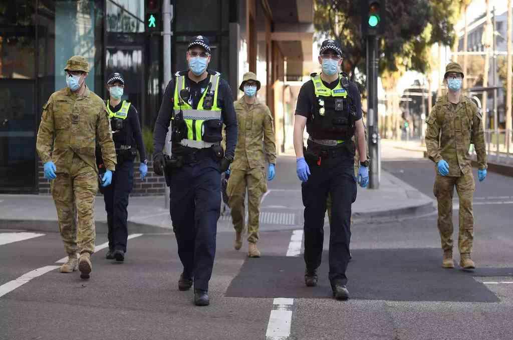 Policías y soldados patrullan en Melbourne, después del anuncio de nuevas restricciones para contener la propagación del nuevo coronavirus. Crédito: AFP