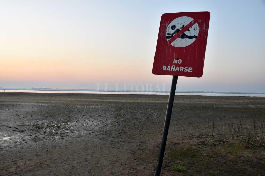 Quedó lejos. ...Y chiquito, el cartel que indica la prohibición de ingresar a la laguna Setúbal, sobre el solarium de la Costanera Oeste, producto de la bajante. Crédito: Flavio Raina