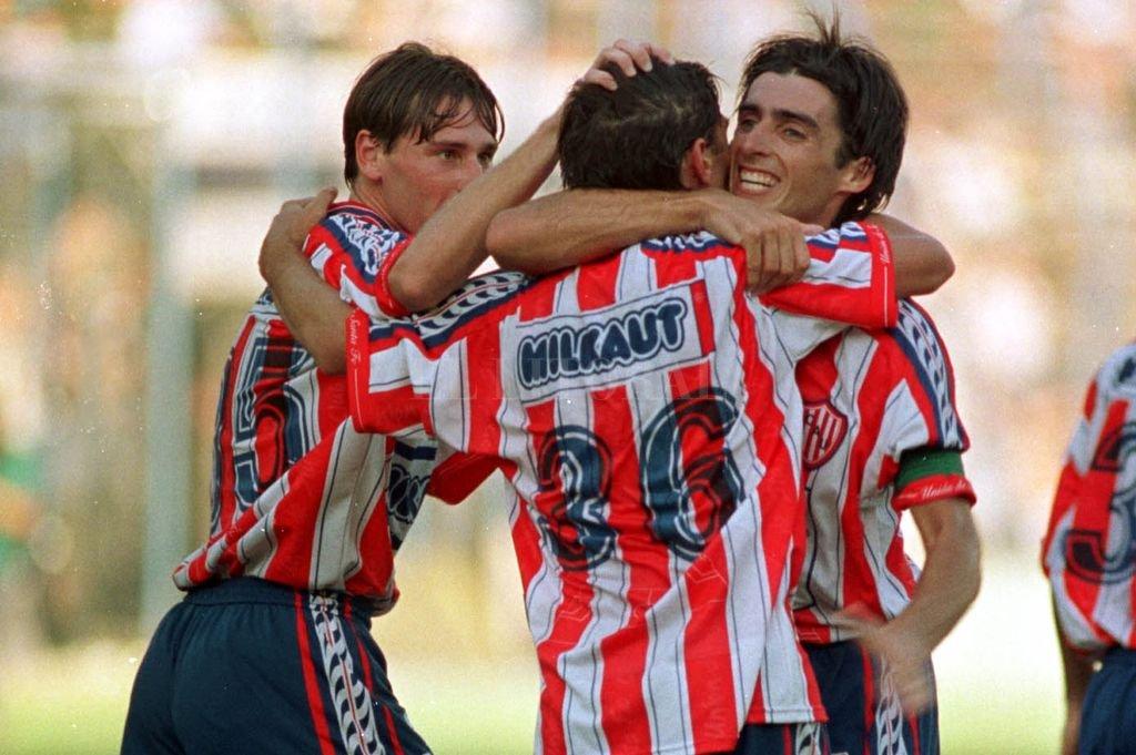 El abrazo del Cabezón Trotta con Valli y Domizzi en el festejo de uno de los goles en aquella buena campaña del 98-99, primero con Mario Zanabria y luego con Salvador Capitano. Crédito: Freddy Heer