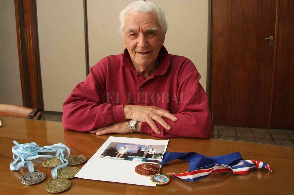 Carlos Busaniche y algunas de las muchas medallas que consiguió a lo largo de su prolífica carrera deportiva. Crédito: Flavio Raina