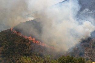 Bomberos combaten las llamas que avanzan sobre un complejo turístico en Córdoba
